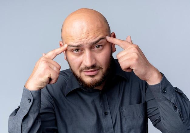 Uomo premuroso giovane call center calvo che mette le dita sulle tempie guardando la parte anteriore isolata sul muro bianco