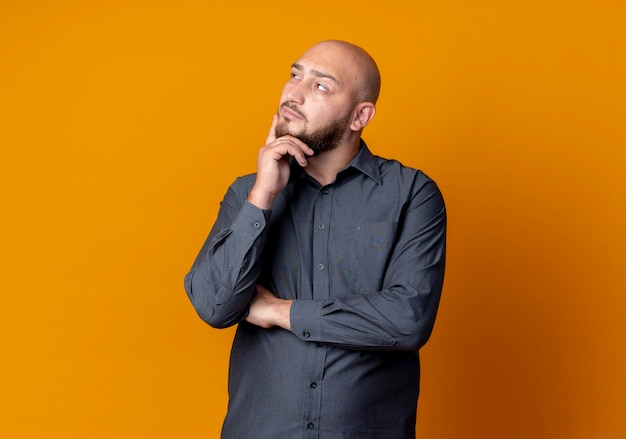 Thoughtful young bald call center man putting hand on chin and looking at side isolated on orange wall
