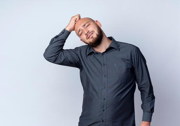 Uomo calvo giovane premuroso della call center che mette la mano sulla testa che esamina la parte anteriore isolata sulla parete bianca