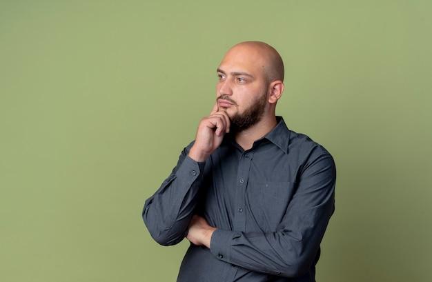 Uomo premuroso giovane call center calvo in piedi con postura chiusa guardando dritto con la mano sul mento isolato sulla parete verde oliva