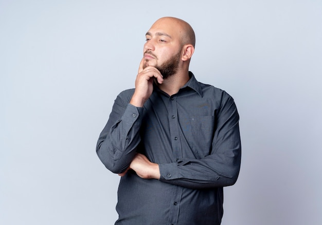 Thoughtful young bald call center man standing with closed posture putting hand on chin looking at side isolated on white wall