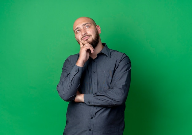 Thoughtful young bald call center man standing with closed posture putting hand on chin looking up isolated on green wall