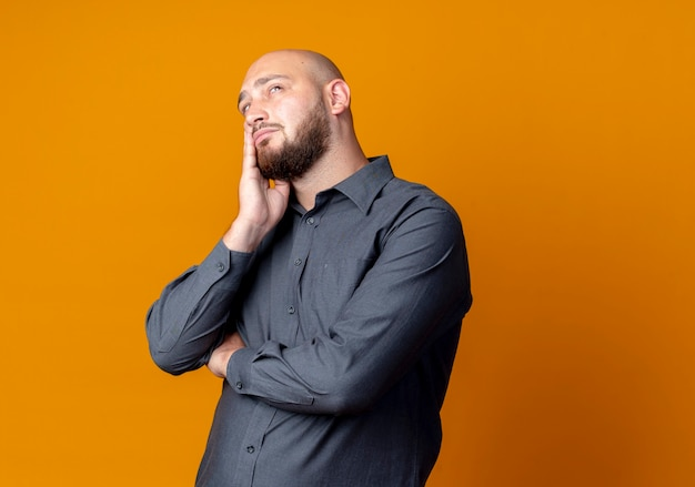 Thoughtful young bald call center man standing with closed posture putting hand on face looking up isolated on orange wall