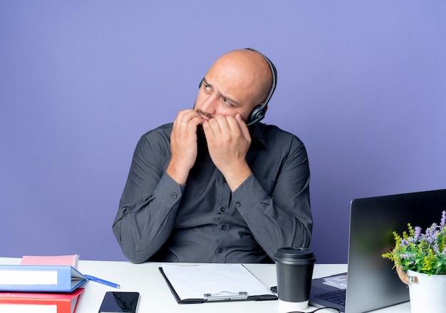 보라색 벽에 고립 된 입술에 손으로 측면을보고 작업 도구로 책상에 앉아 헤드셋을 착용하는 사려 깊은 젊은 대머리 콜 센터 남자