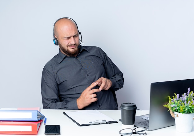 Thoughtful young bald call center man wearing headset sitting at desk with work tools keeping fingers together isolated on white wall