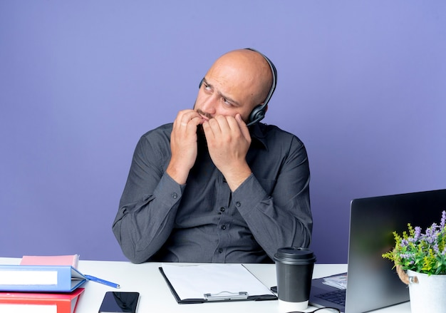 Thoughtful young bald call center man wearing headset sitting at desk with work tools looking at side with hands on lips isolated on purple wall