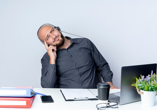 Thoughtful young bald call center man wearing headset sitting at desk with work tools putting finger on temple looking up isolated on white wall