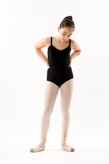 Thoughtful young ballerina with hands on hips