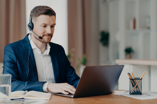 Вдумчивый молодой бородатый бизнесмен в стильном костюме делает онлайн-звонок или принимает участие в веб-конференции, используя ноутбук и наушники с микрофоном. удаленная работа дома и бизнес-концепция