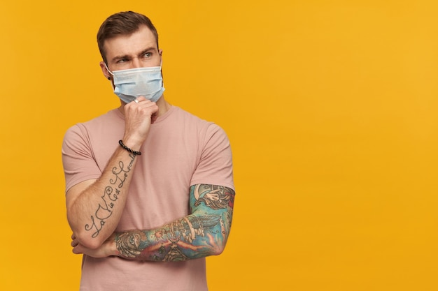 Thoughtful young bearded man with tattoo on hand in pink tshirt and hygienic mask to prevent infection keeps hand on chin and thinking over yellow wall