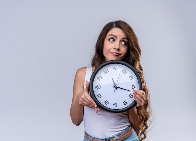 Giovane bella ragazza premurosa che tiene orologio che esamina il lato destro sulla parete bianca isolata con lo spazio della copia