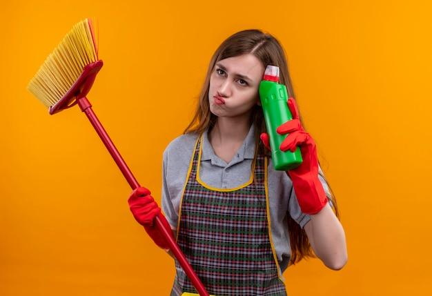 エプロンとゴム手袋でモップと掃除用品を持っている思いやりのある若い美しい少女は、不機嫌そうに見えて、考えています