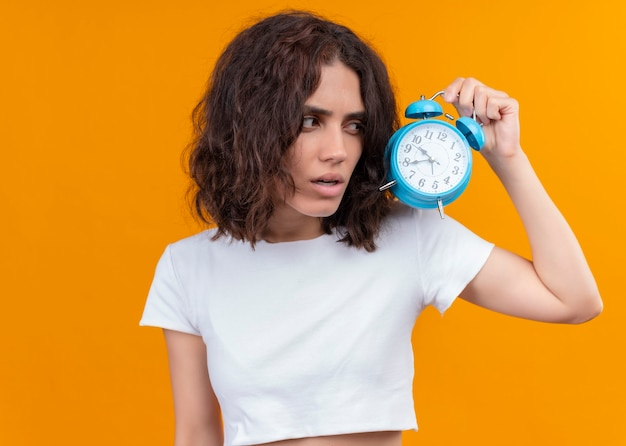 Thoughtful young beautiful woman holding alarm clock on isolated orange wall with copy space