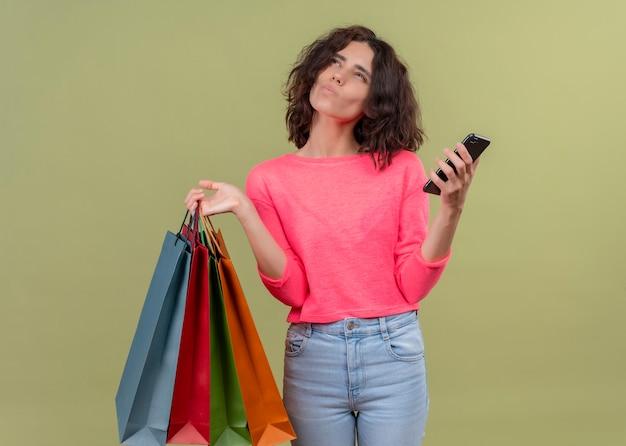 Giovane bella donna premurosa che tiene i sacchetti di cartone e il telefono cellulare sulla parete verde isolata