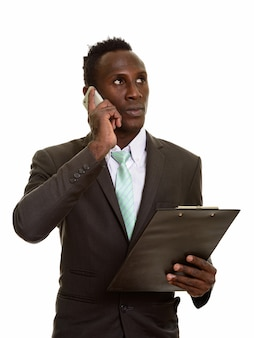 Thoughtful young black african businessman talking on mobile phone