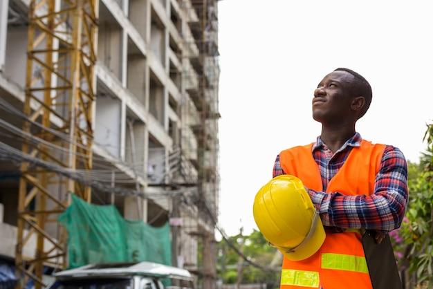 Задумчивый молодой темнокожий африканец на стройке
