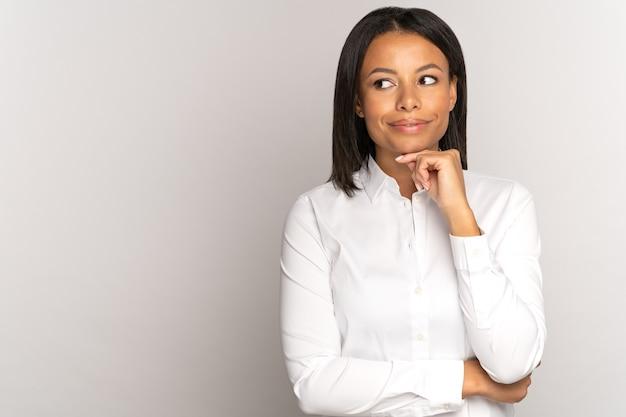 思いやりのある若い黒人女性は、笑顔で取引の成功を考えて見ているあごの実業家に触れます