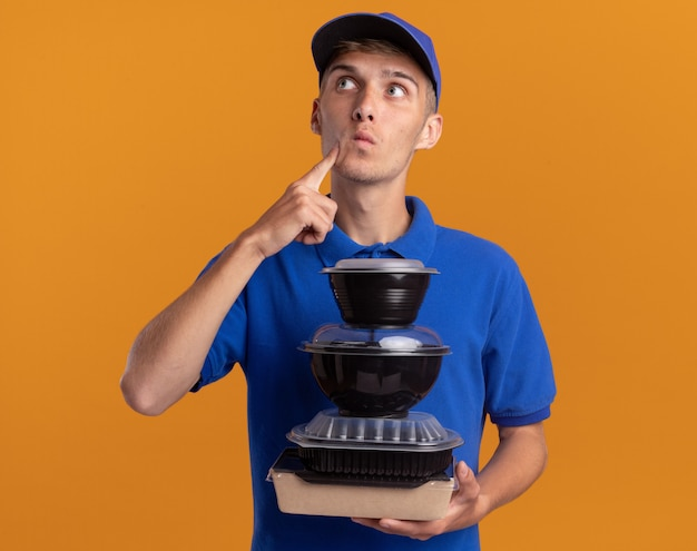 Thoughtful young blonde delivery boy puts finger on chin and holds food containers looking up isolated on orange wall with copy space