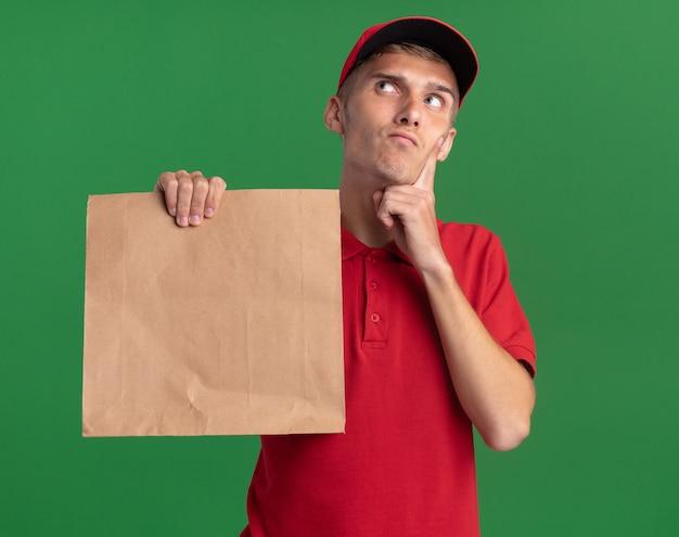 Il giovane ragazzo biondo premuroso delle consegne mette il dito sul mento e tiene il pacchetto di carta guardando in alto isolato sulla parete verde con spazio copia