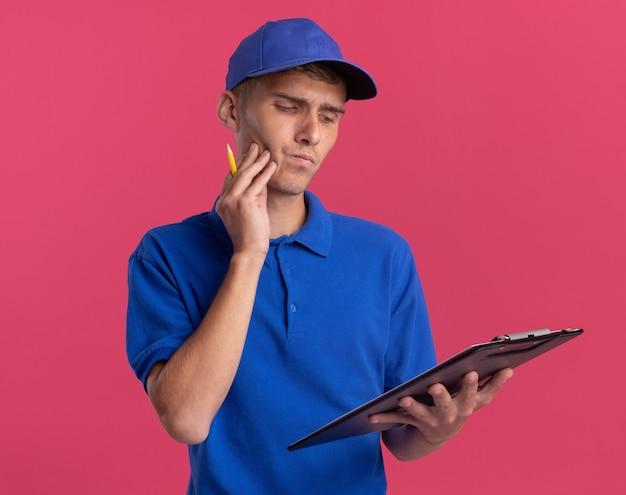 Il giovane ragazzo biondo premuroso delle consegne mette la mano sul viso tenendo e guardando la lavagna per appunti isolata sulla parete rosa con spazio di copia