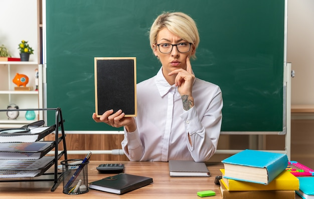 사려깊은 젊은 금발 여교사는 교실에서 학용품을 들고 책상에 앉아 앞을 바라보며 턱에 손을 대고 있는 미니 칠판을 보여줍니다.