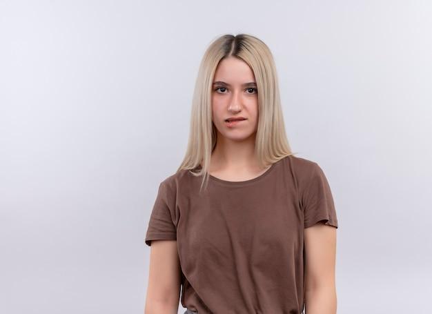 Giovane ragazza bionda premurosa che morde il suo labbro che sta sulla parete bianca isolata con lo spazio della copia