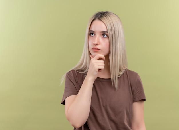 복사 공간이 격리 된 녹색 벽에 턱에 손을 넣어 사려 깊은 젊은 금발 소녀