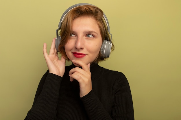 Thoughtful young blonde girl wearing headphones touching chin and headphones looking at side plunging into dreams isolated on olive green wall with copy space