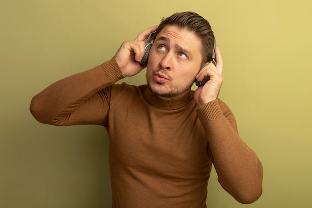 사려깊은 젊은 금발의 잘생긴 남자가 헤드폰을 끼고 올리브 녹색 벽에 고립되어 올려다보고 있습니다.