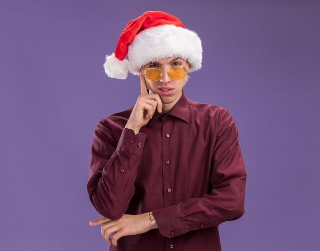 サンタの帽子とメガネを身に着けている思いやりのある若いブロンドの男は、紫色の背景に分離された思考ジェスチャーを行うカメラを見て