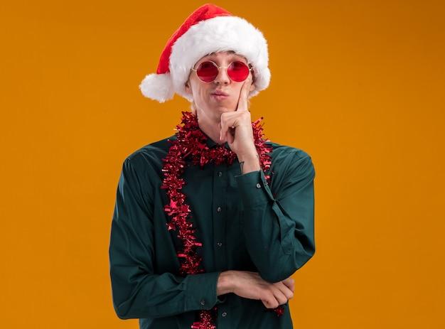 Riflessivo giovane uomo biondo che indossa santa cappello e occhiali con tinsel ghirlanda intorno al collo guardando la telecamera tenendo la mano sul mento isolato su sfondo arancione con spazio di copia