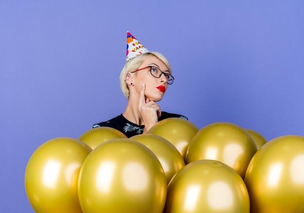 紫の背景で隔離の感動的な顔を見上げて風船の後ろに立っている眼鏡と誕生日の帽子を身に着けている思いやりのある若いブロンドのパーティーの女の子
