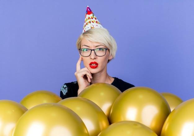 Premurosa ragazza bionda giovane partito con gli occhiali e cappello di compleanno in piedi dietro palloncini toccando il viso che guarda l'obbiettivo isolato su sfondo viola