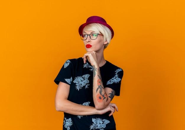 Premurosa giovane bionda party girl indossando party hat e bicchieri mettendo la mano sotto il mento guardando il lato isolato su sfondo arancione con copia spazio