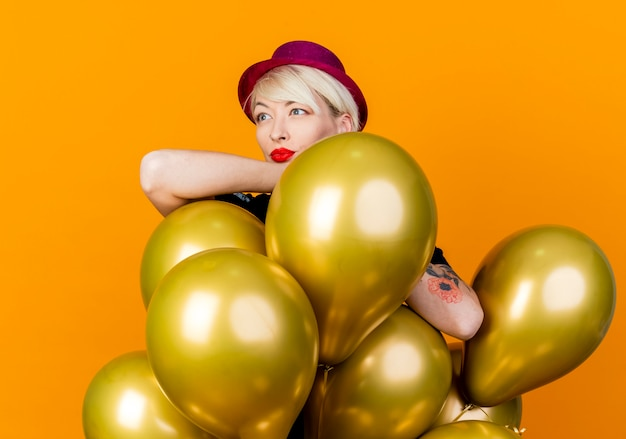Thoughtful young blonde party girl wearing party hat standing behind balloons putting arms on them looking at side isolated on orange background