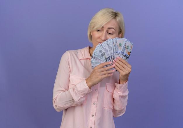 Riflessivo giovane bionda donna slava tenendo i soldi vicino al viso guardando il lato isolato su sfondo viola con copia spazio