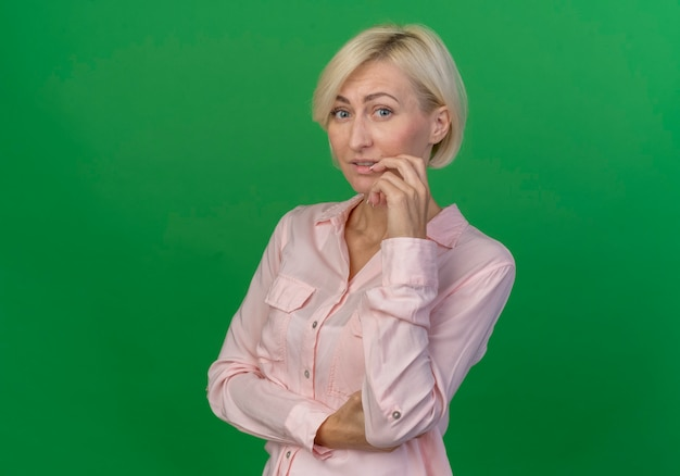 Thoughtful young blonde slavic woman touching face looking at camera isolated on green background with copy space