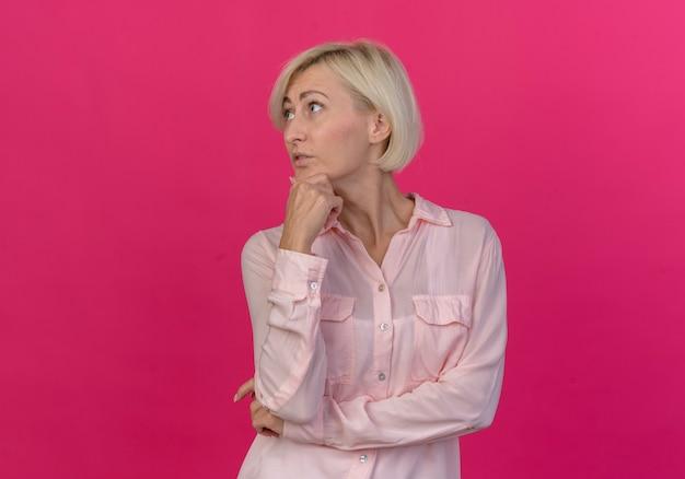 Premurosa bionda giovane donna slava girando la testa a lato mettendo la mano sul mento guardando il lato isolato su sfondo rosa con spazio di copia