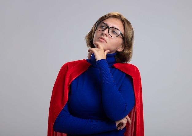 白い背景で隔離の側を見てあごに触れる眼鏡をかけている赤いマントの思いやりのある若いブロンドのスーパーヒーローの女の子
