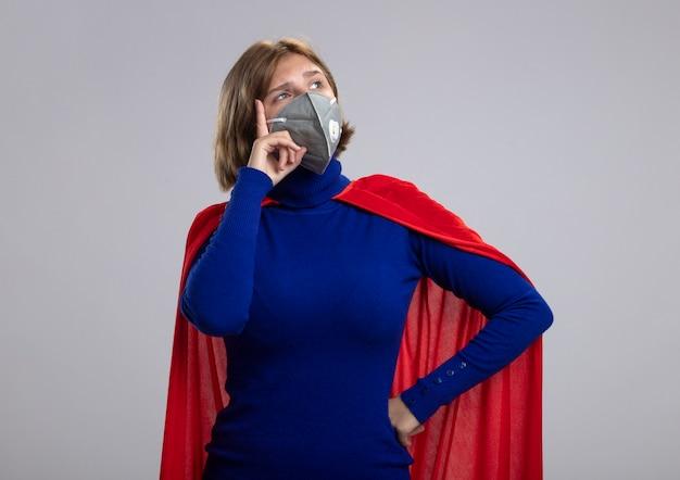 保護マスクを身に着けている赤いマントの思いやりのある若いブロンドのスーパーヒーローの女の子は、白い背景で隔離の思考ジェスチャーをしている側を見て腰に手を保ちます