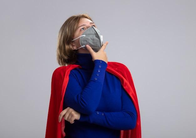 Riflessivo giovane bionda ragazza del supereroe in mantello rosso che indossa la maschera protettiva cercando di ritoccare isolato su sfondo bianco con copia spazio