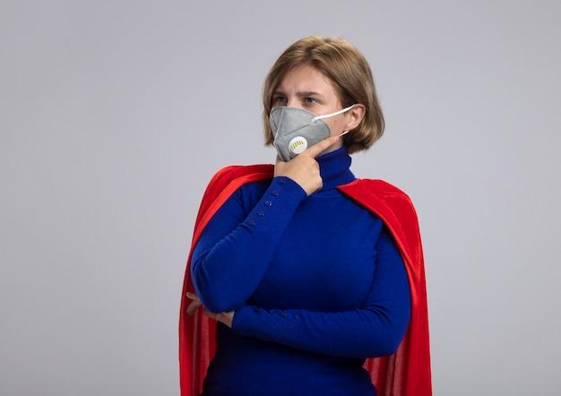 Premurosa bionda giovane supereroe ragazza in mantello rosso che indossa la maschera protettiva toccando il mento guardando il lato isolato su sfondo bianco con spazio di copia