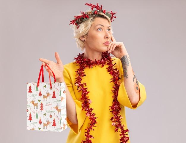 クリスマスの頭の花輪と首の周りに見掛け倒しの花輪を身に着けている思いやりのある若いブロンドの女性は、白い背景で隔離の思考ジェスチャーをしている側を見てクリスマスギフトバッグを保持しています