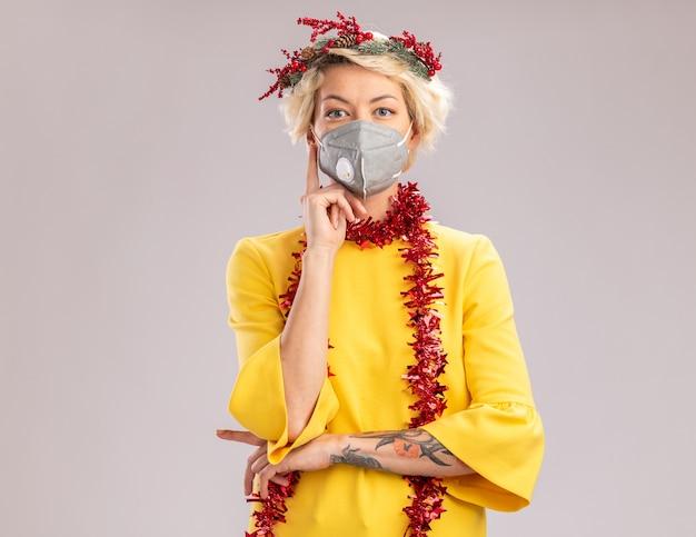 Premurosa giovane donna bionda che indossa la testa di natale ghirlanda e tinsel ghirlanda intorno al collo con maschera protettiva guardando la telecamera tenendo la mano sul mento isolato su sfondo bianco con spazio di copia