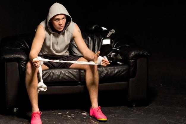 暗闇の中でパーカーを着て、手に包帯を巻いて座っている思いやりのある若いボクサー