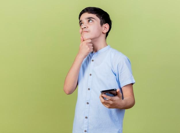 Giovane ragazzo premuroso che tiene telefono mobile che tocca il mento che osserva in su isolato sulla parete verde oliva