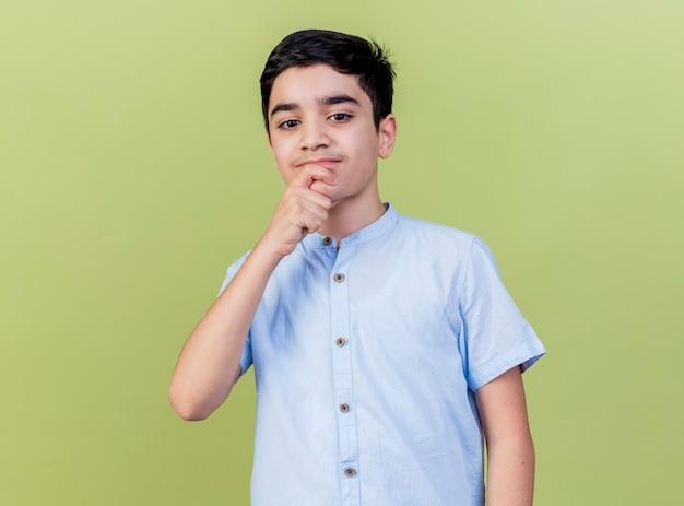 올리브 녹색 벽에 격리 내려다보고 턱에 손을 넣어 사려 깊은 어린 소년