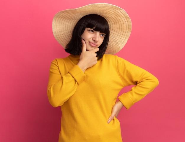 Задумчивая молодая брюнетка кавказская девушка в пляжной шляпе держит подбородок и смотрит в сторону