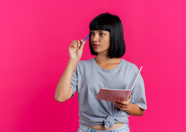 La giovane donna caucasica castana premurosa mette la penna sul tempiale e tiene il taccuino che esamina il lato isolato su fondo rosa con lo spazio della copia