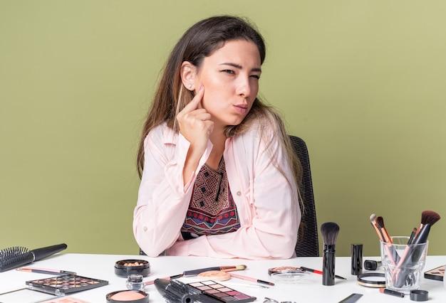 Задумчивая молодая брюнетка девушка сидит за столом с инструментами для макияжа, глядя в сторону